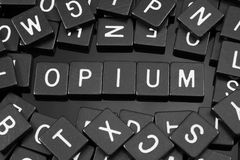 Black letter tiles spelling the word & x22;opium& x22; Royalty Free Stock Photos