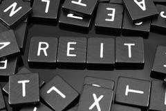 Black letter tiles spelling the word & x22;REIT& x22; Stock Image