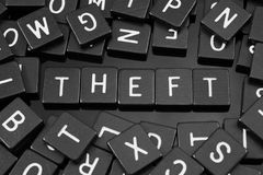Black letter tiles spelling the word & x22;theft& x22; Stock Images