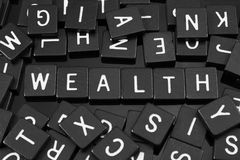 Black letter tiles spelling the word & x22;wealth& x22; Royalty Free Stock Photos