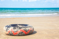 Black lifebuoy on the sand Stock Photos