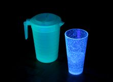 Black-light Objects. A pitcher and a cup under a black light royalty free stock image