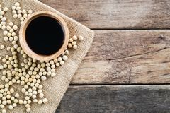Black light soy sauce in wooden bowl with soy bean on gunny sack cloth royalty free stock images