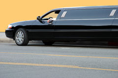 Black limousine. The Limousine driver waiting orange background Royalty Free Stock Image