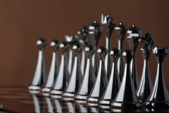Black line chess figures. The photo shows the chessboard with metal figures Royalty Free Stock Image