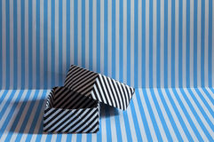 Black lined origami box on blue lined background texture Royalty Free Stock Images