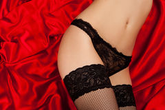 Black lingerie on red silk Stock Photos
