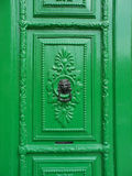 Black Lion Head Iron Knocker on Green Door. Traditional style black wrought iron doorknocker adorning an ornately carved emerald green door in Malta Stock Photos