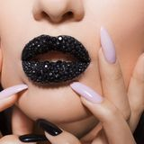 Black lips covered with rhinestones. Beautiful woman with Black lipstick on her lips and black and white manicure royalty free stock photography
