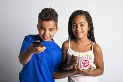 Black little boy and girl watching movie with pop corn Royalty Free Stock Image