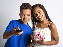 Black little boy and girl watching movie with pop corn Stock Photos