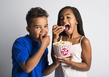 Black little boy and girl watching movie with pop corn Royalty Free Stock Images
