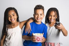Black little boy and sister girl watching movie with pop corn Stock Image