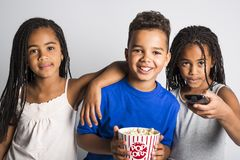 Black little boy and sister girl watching movie with pop corn Stock Photo