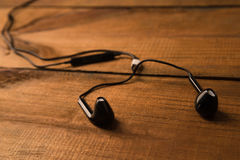 Black little headphones on a wooden isolated background. Horizontal frame Royalty Free Stock Photos