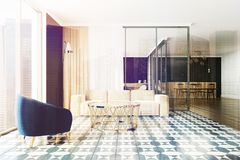 Black living room and dining room toned. Modern living room with black walls, a tiled floor, a white sofa and a blue armchair. A dining room in the background Stock Images