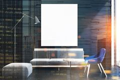 Black living room interior, gray sofa, poster double. Upscale living room interior with black walls and a concrete floor. A soft light gray sofa and a blue chair Stock Images