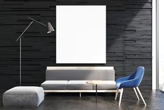 Black living room interior, gray sofa, poster. Upscale living room interior with black walls and a concrete floor. A soft light gray sofa and a blue chair. A Stock Photography