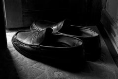Black loafers. Ajar door illuminating black loafers Royalty Free Stock Photo