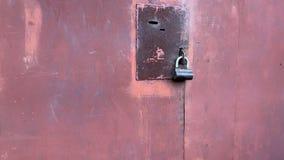 Black lock hanging on a rusty metal door