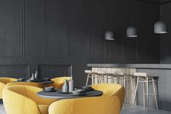 Black loft cafe coner with a bar. Black cafe corner with a concrete floor, round black tables and yellow chairs. A bar with stools. 3d rendering mock up Stock Image
