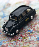 Black London taxi cab on map of London. Black model London taxi cab on map of London royalty free stock image