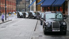 A black London taxi cab pulls away from a row of waiting black cabs at a taxi rank outside of King`s Cross St. Pancras Railway