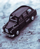 Black London taxi cab on street map of London Royalty Free Stock Image