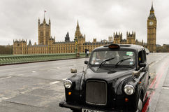 Black London taxi in front of Big Ben royalty free stock photography