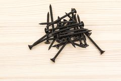 Black screws lying on a wooden surface stock image
