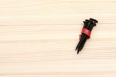 Black long screws tied with a red plastic strip lie on a wooden surface royalty free stock photography