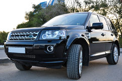 Black luxurious SUV. Luxurious black SUV standing in the summer sunset in front of skyscrapers royalty free stock photos