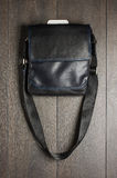 Black luxury leather male handbag hanged on the wall Royalty Free Stock Images
