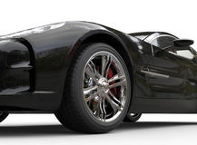 Black luxury sports car on white background - wheel close up. Stock Photo