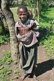 Black Maasai boy carries on the back a little sister. Royalty Free Stock Image