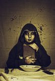 Black magic. Bloody cultist with the Satanic Bible over dirty background Royalty Free Stock Image