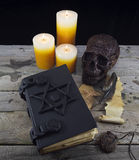 Black magic book with mystic objects Royalty Free Stock Photos