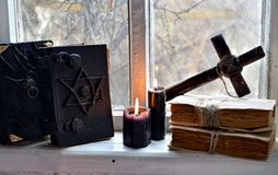 Black magic books, black candles and cross against old window. Occult, esoteric, divination and wicca concept. Mystic and vintage background with old objects royalty free stock image