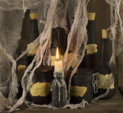 Black magic bottles with candle. Group of black bottles with burning candle on wooden background Royalty Free Stock Images