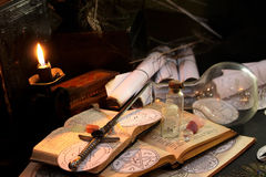 Black Magic Ritual. Antique Magic Book. Witchcraft  background. Candle and alchemy ingredients around Stock Images