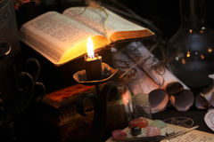 Black Magic Ritual. Antique Magic Book. Witchcraft  background. Candle and alchemy ingredients around Stock Image