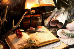 Black Magic Ritual. Antique Magic Book. Witchcraft  background. Candle and alchemy ingredients around Stock Photos