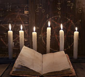 Black magic ritual with burning candles and open book against wooden background Royalty Free Stock Photo