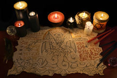 Black magic ritual with demon manuscript and evil candles Royalty Free Stock Photo