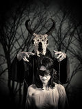 Black magic sacrifice. Blindfolded women and scary men with cow skull head royalty free stock photography