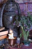 Black Magic Spells. Wiccan spells and herbs. Still Live: Old oil lamps, antique books, dried rose buds, a burning candle in a copper bowl, medicine bottles Stock Photography