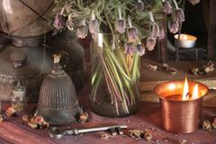 Black Magic Spells. Wiccan spells and herbs. Still Live: Old oil lamps, antique books, dried rose buds, a burning candle in a copper bowl, medicine bottles Royalty Free Stock Photography