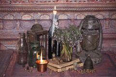 Black Magic Spells. Wiccan spells and herbs. Still Live: Old oil lamps, antique books, dried rose buds, a burning candle in a copper bowl, medicine bottles Stock Photos