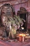 Black Magic Spells. Wiccan spells and herbs. Still Live: Old oil lamps, antique books, dried rose buds, a burning candle in a copper bowl, medicine bottles Royalty Free Stock Photo