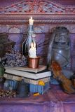 Black Magic Spells. Wiccan spells. Still Live: Old oil lamps, antique books, dried rose buds, a burning candle in a copper bowl, medicine bottles, lavender Stock Photos